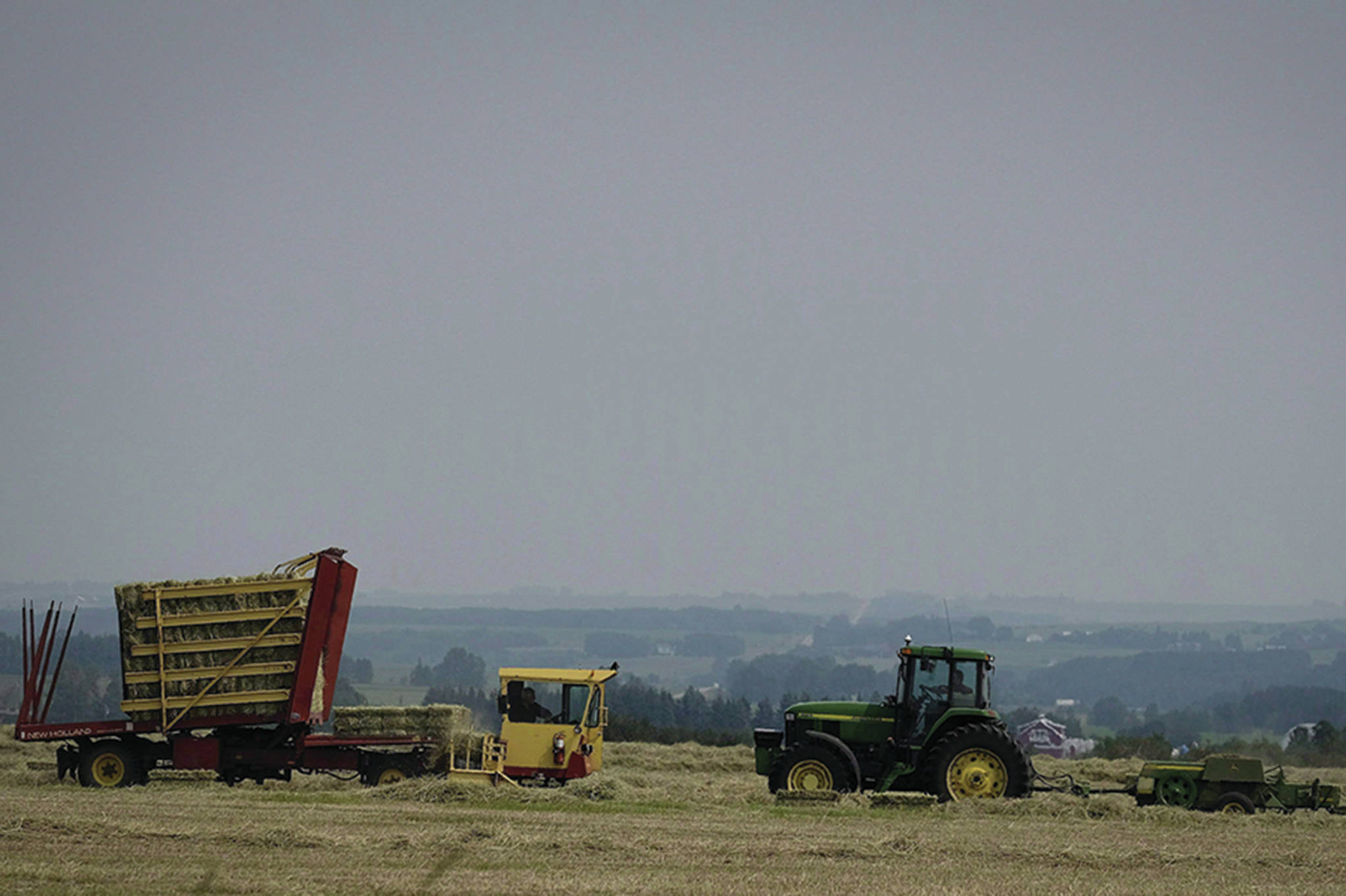 Farmer Grant Bird, left, and farm hand Connor Hunt bale a hay crop near Cremona, Alta., Monday, July 17, 2017.Farmers are on a never-ending quest for more detailed weather forecasts as they try to increase yields on larger plots while contending with more extreme weather, such as the record rains that have drenched parts of southern Ontario this year, or the droughts that have left vast fields bone dry in Saskatchewan. THE CANADIAN PRESS/Jeff McIntosh